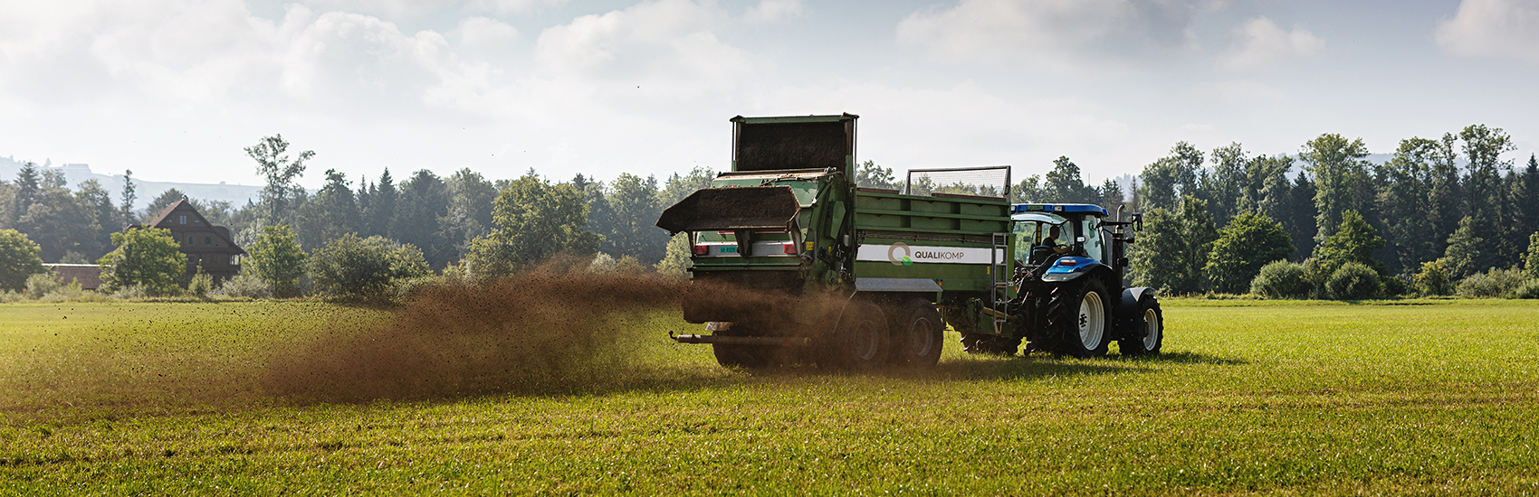 Ausstreuen von Kompost auf dem Feld mit dem Traktor für einen Kunden von Qualikomp AG in Emmen